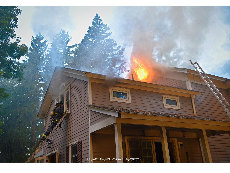 A firefighter on a ladder as fire vents from an upper floor.