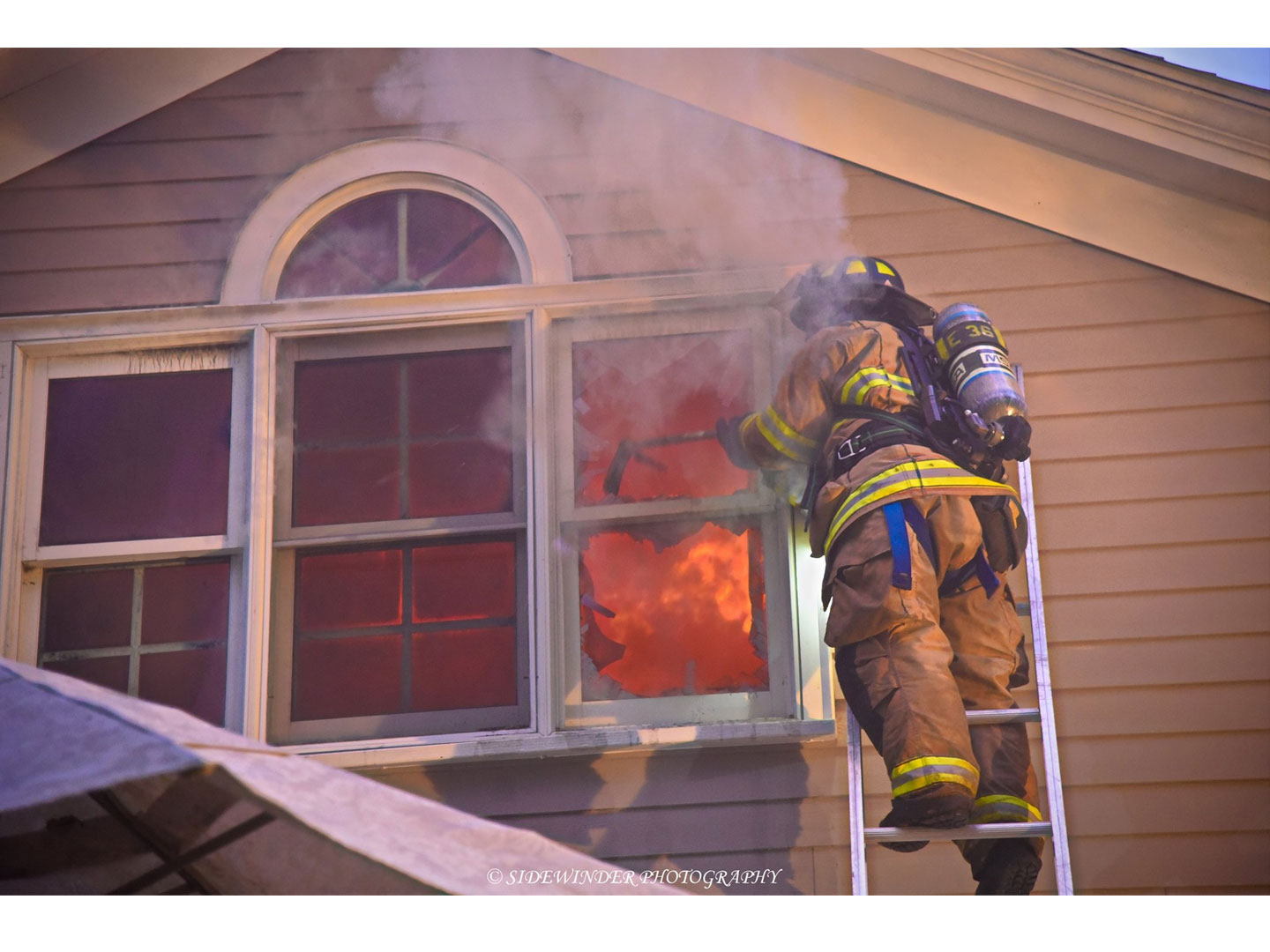 Fire rages inside the home as a firefighter operates on a ladder.