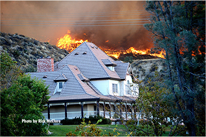 Fire threatens a home