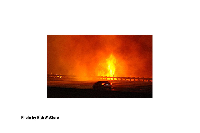 Flames roar by a roadway
