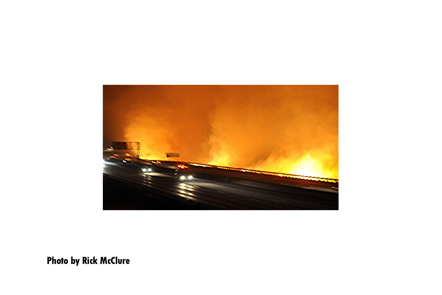 Cars passing by as flames from the Tick Fire roar nearby