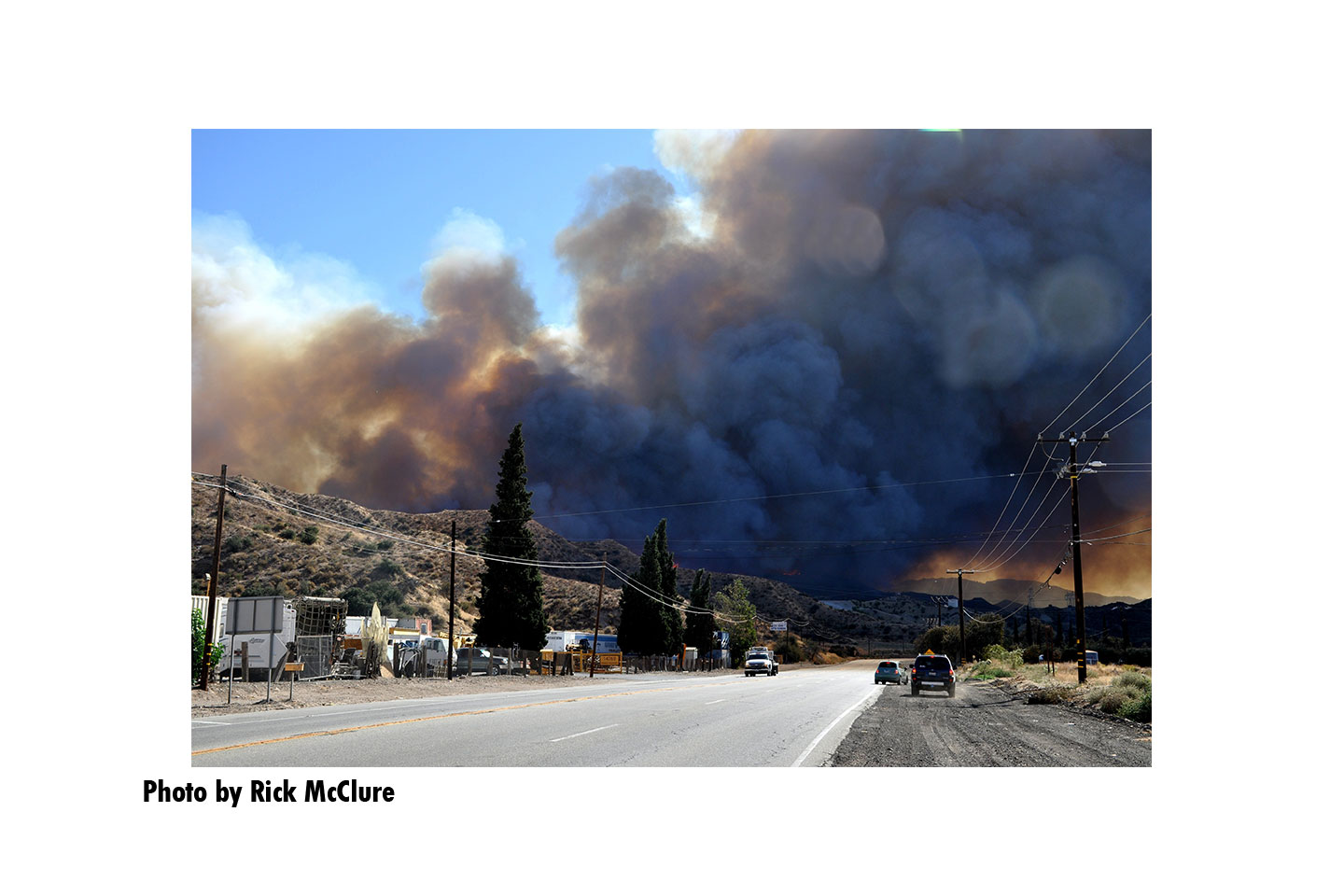 A giant plume of smoke hangs over the road