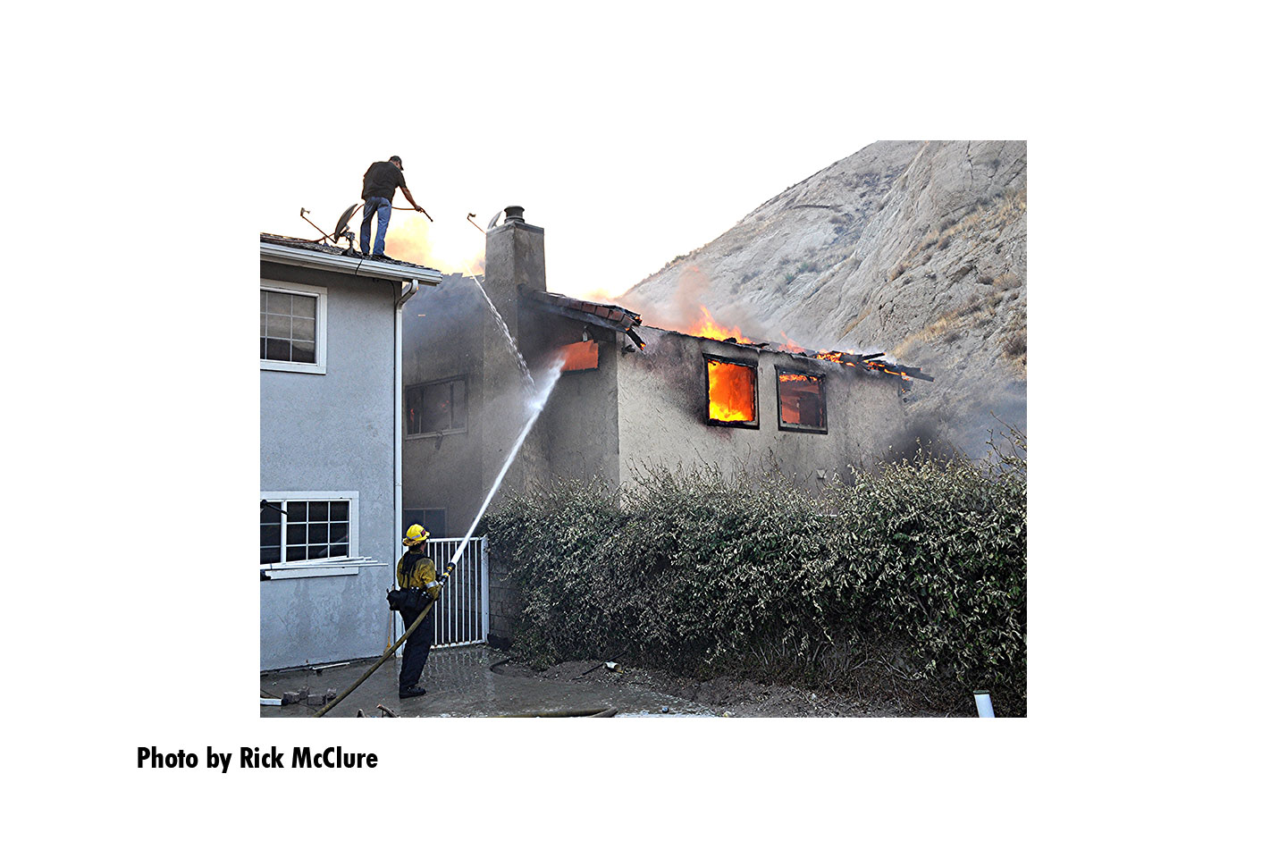 At the Tick Fire, firefighters direct a hosestream into a burning building