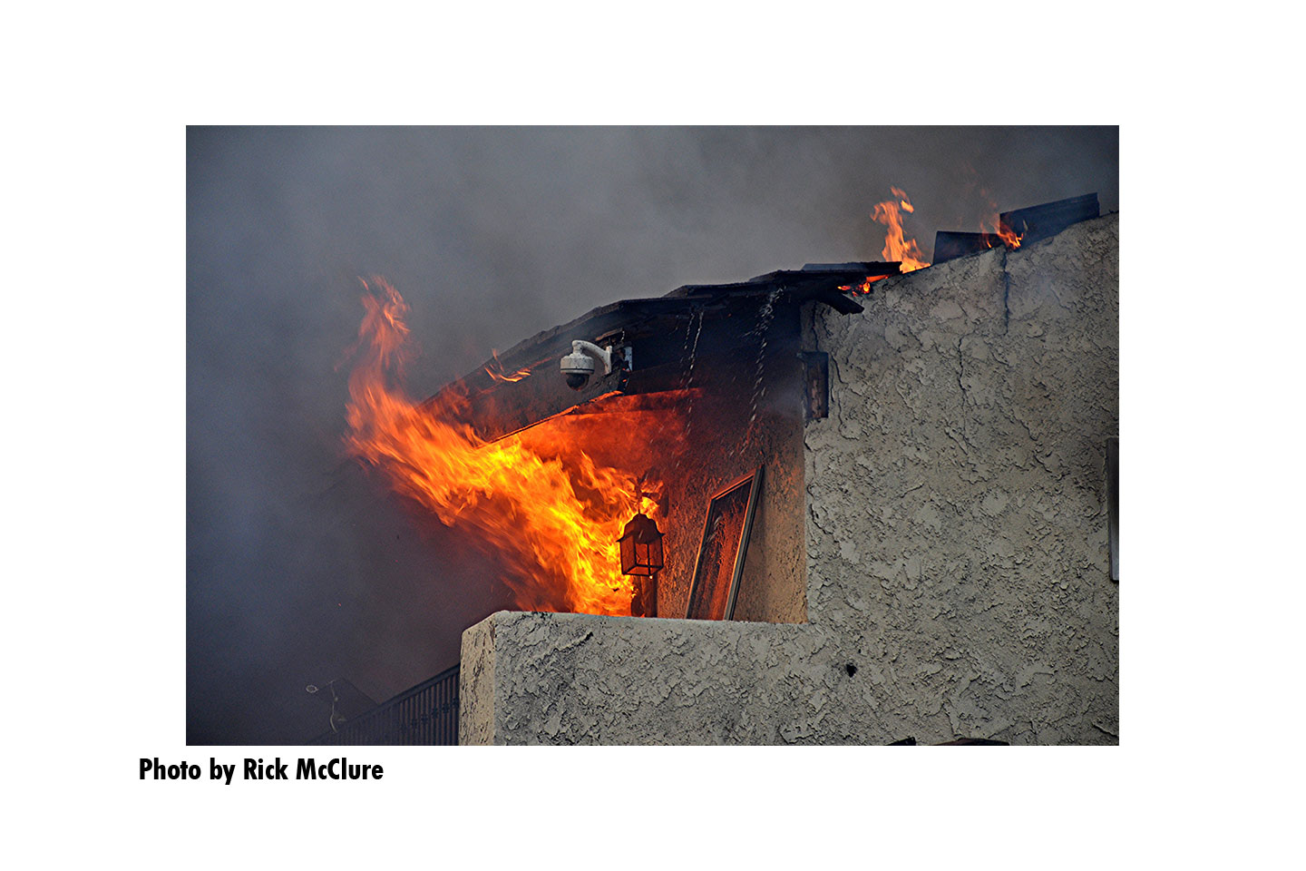 Flames and smoke engulf a building