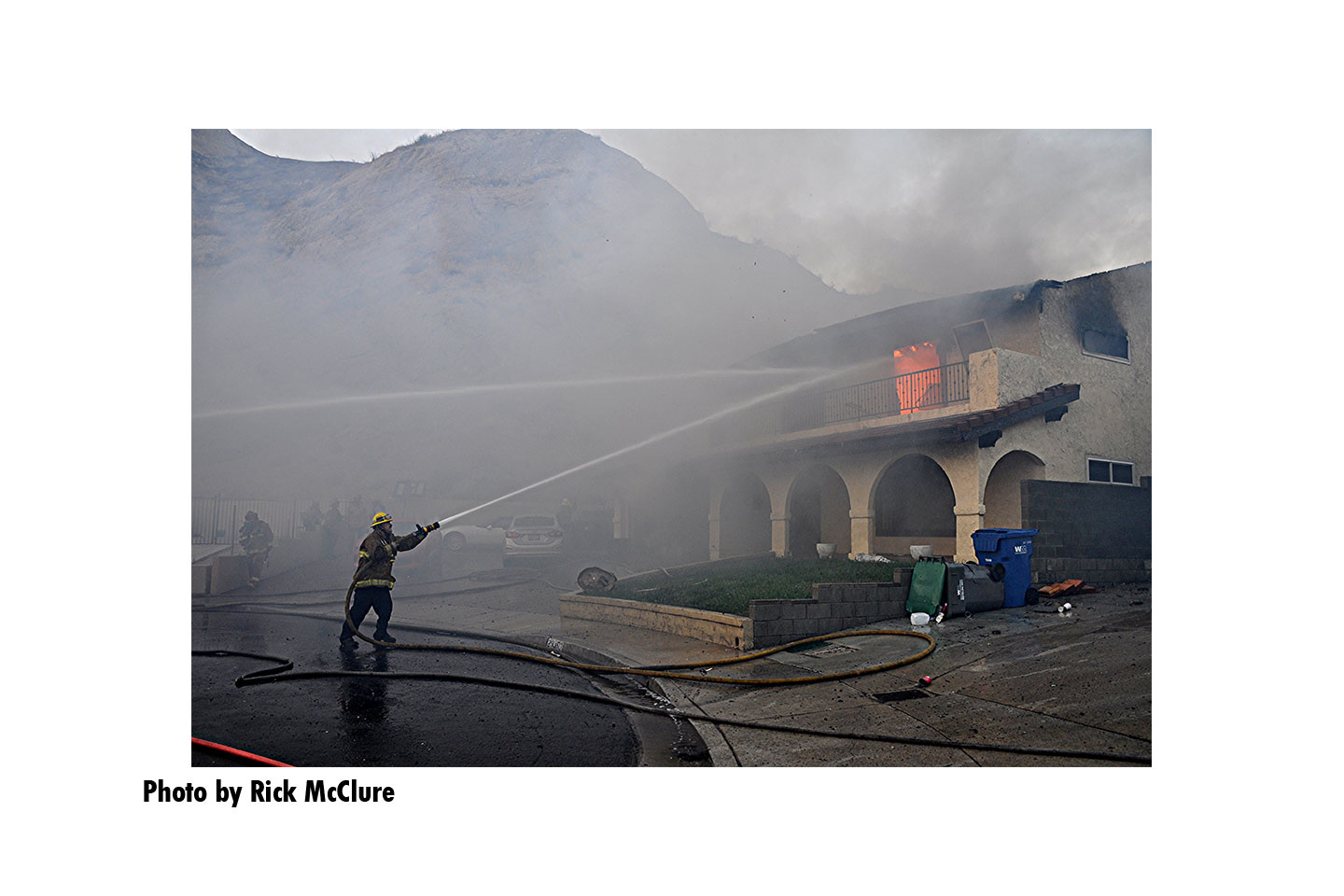 Firefighters direct streams onto a burning building during the Tick Fire