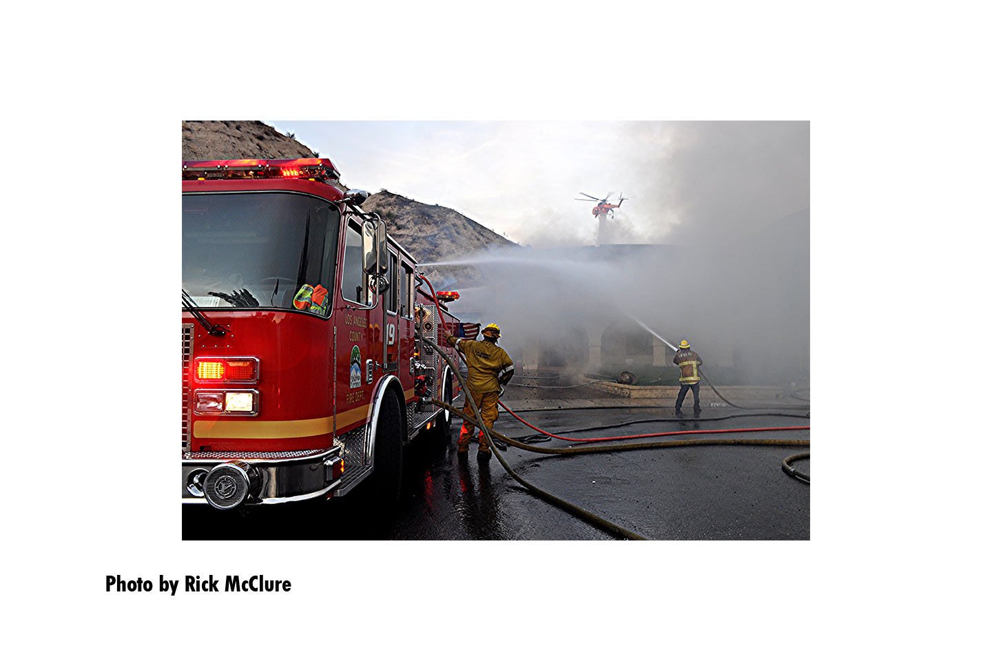 Fire apparatus with firefighters and streams with a helicopter in the background