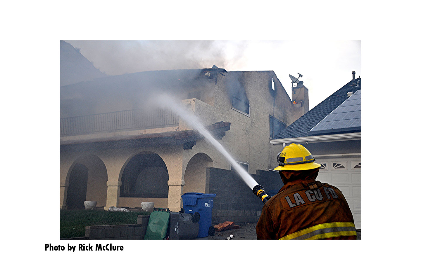 A Los Angeles County Fire Department member aims a hose stream onto a burning residence