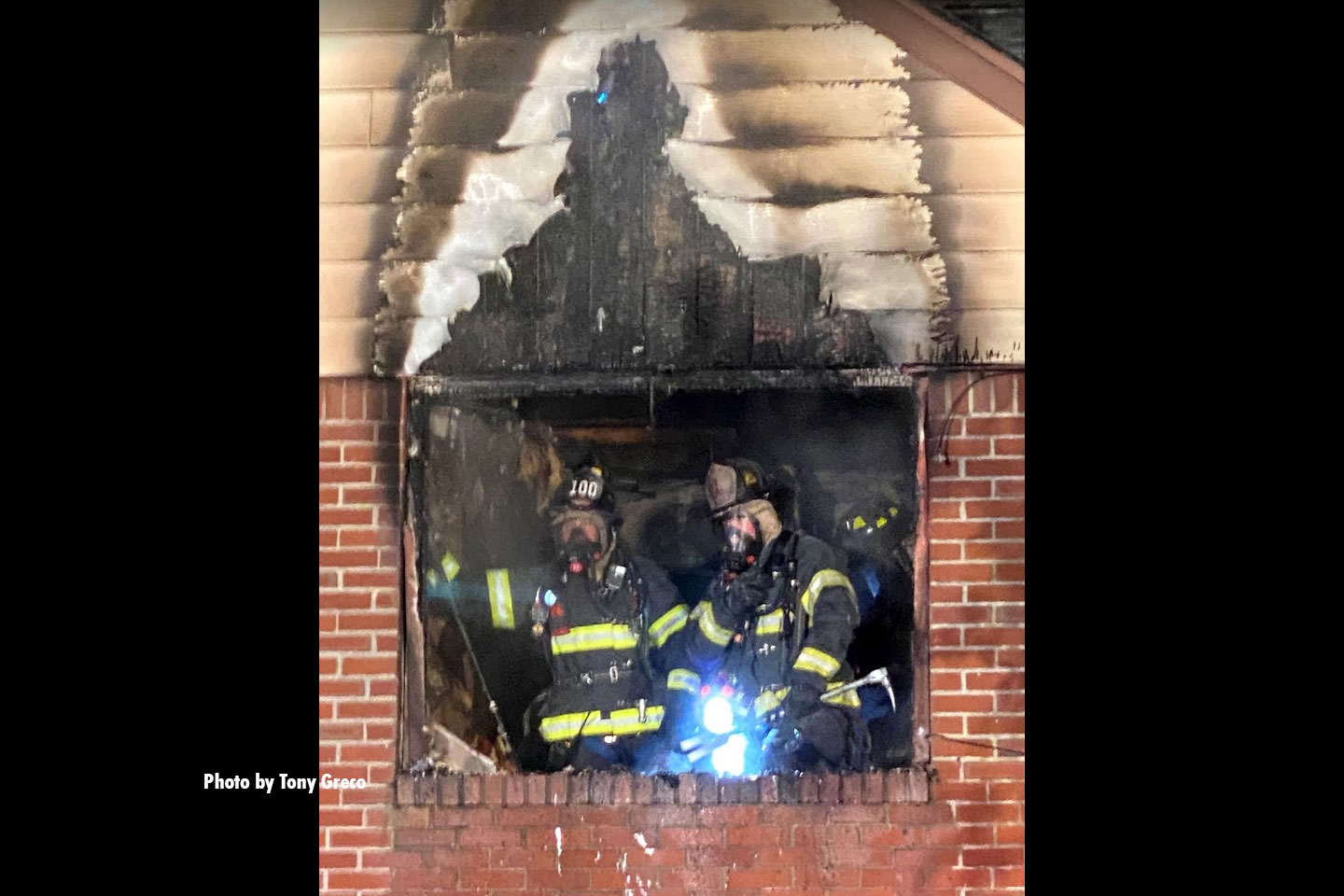 Firefighters at a window during fire operations in Teaneck, New Jersey.