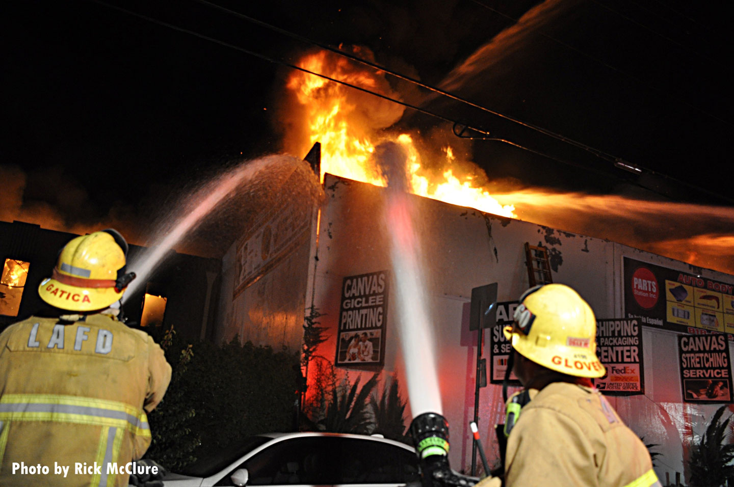 Los Angeles Fire Department firefighters aim hose streams on the fire.