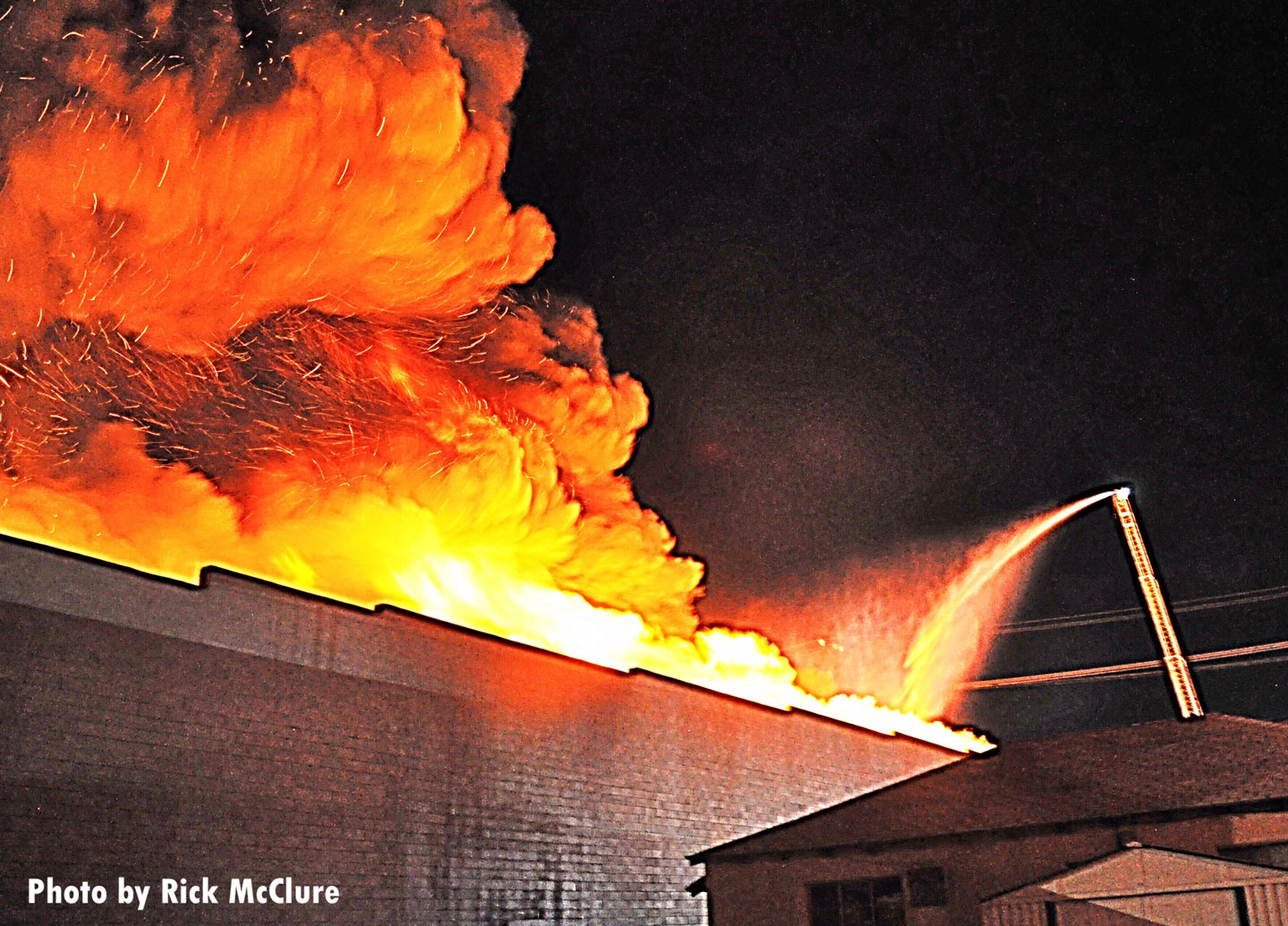 Flames shoot skyward from the fire building