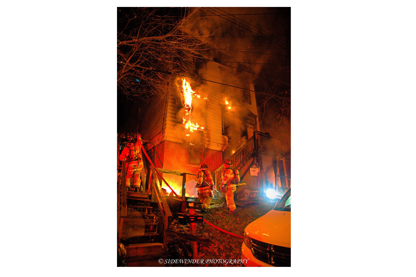 Firefighters advance hoselines at a two-alarm Troy fire.