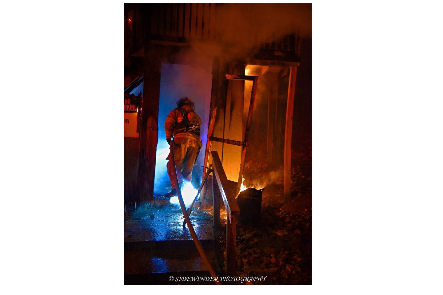 A firefighter advances a hoseline into the structure.