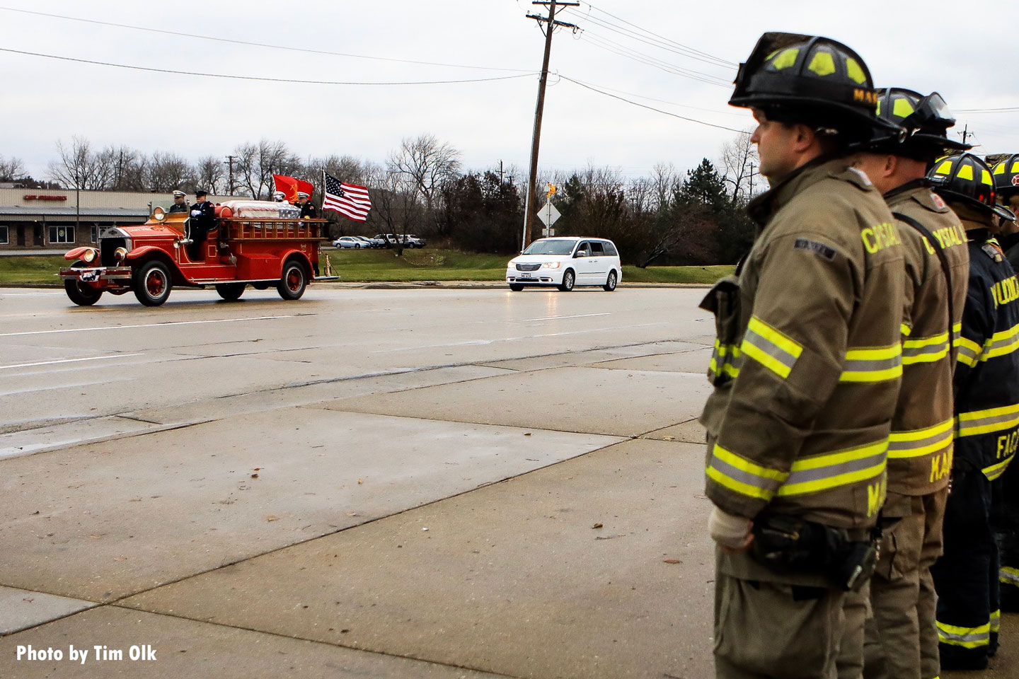 Firefighters stand at attention as the rig passes by.