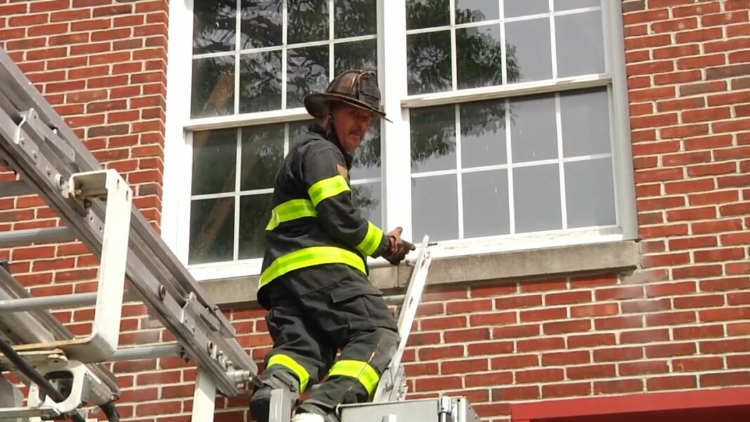 Mike Ciampo on extension ladder mounted on tower ladder