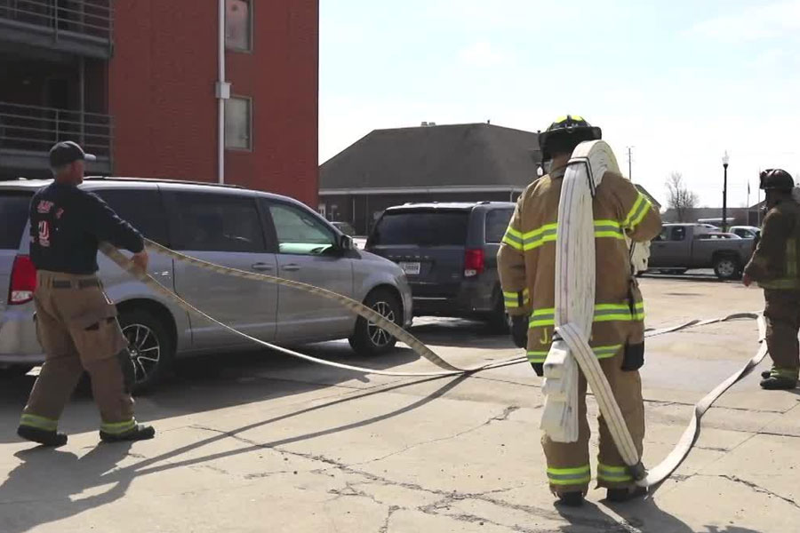 Firefighters flake out hoselines to navigate between parked cars