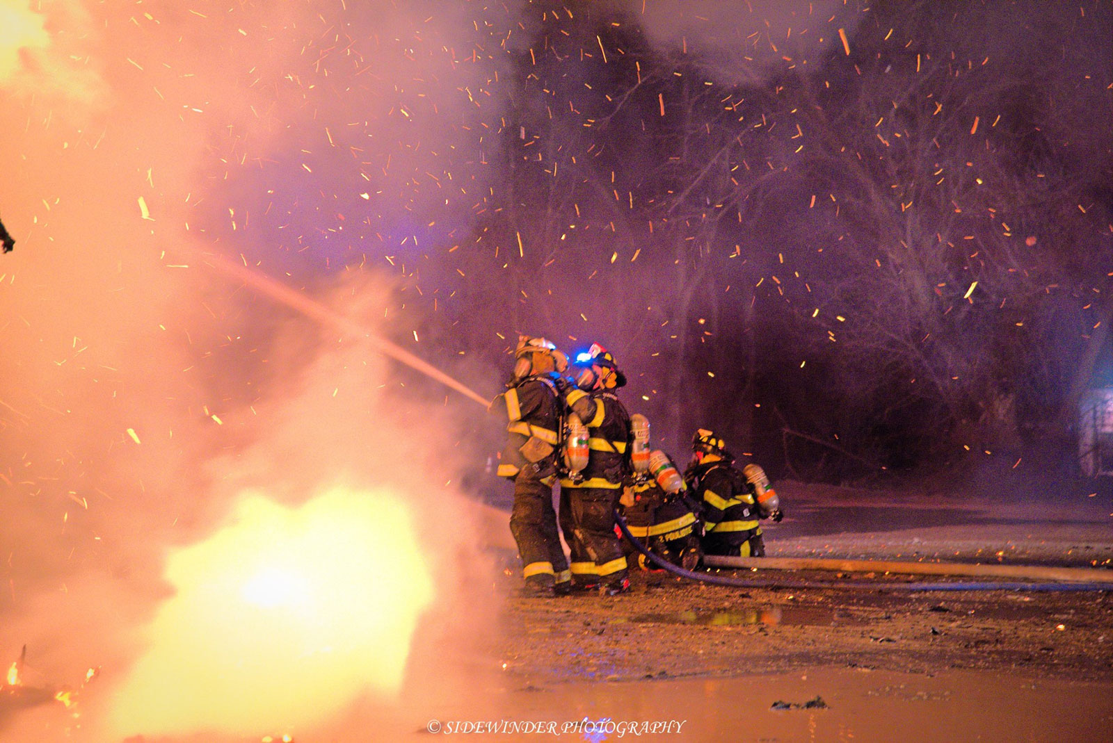 Several firefighters, surrounded by sparks, coordinate an exterior line