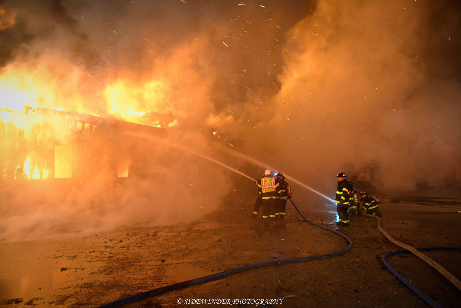Firefighters aim two hoselines at the burning commercial garage