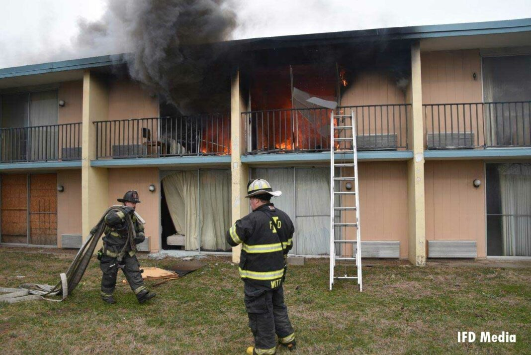 Firefighter brings hoseline to ground ladder at motel fire