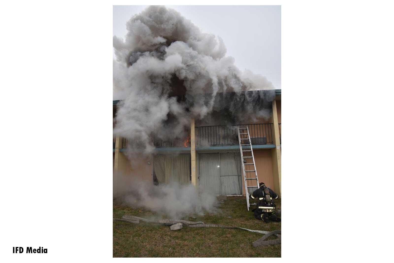 Billowing grey smoke and ground ladder