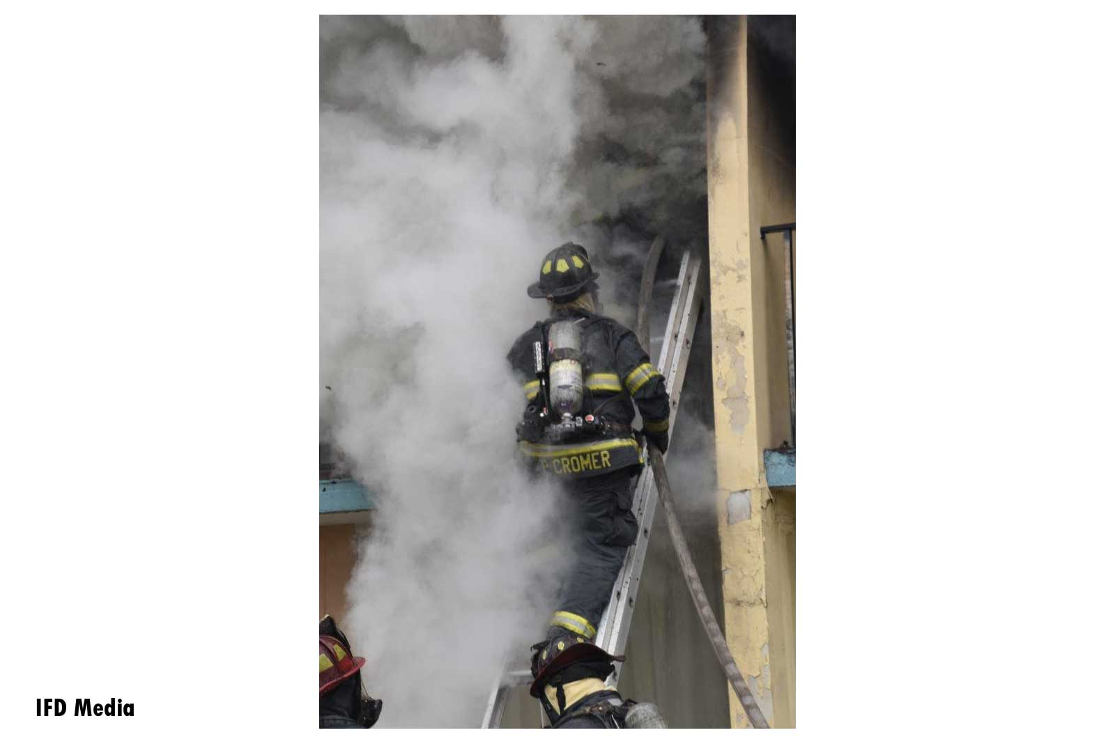 Firefighter stretches hoseline up a portable ladder to second-floor balcony