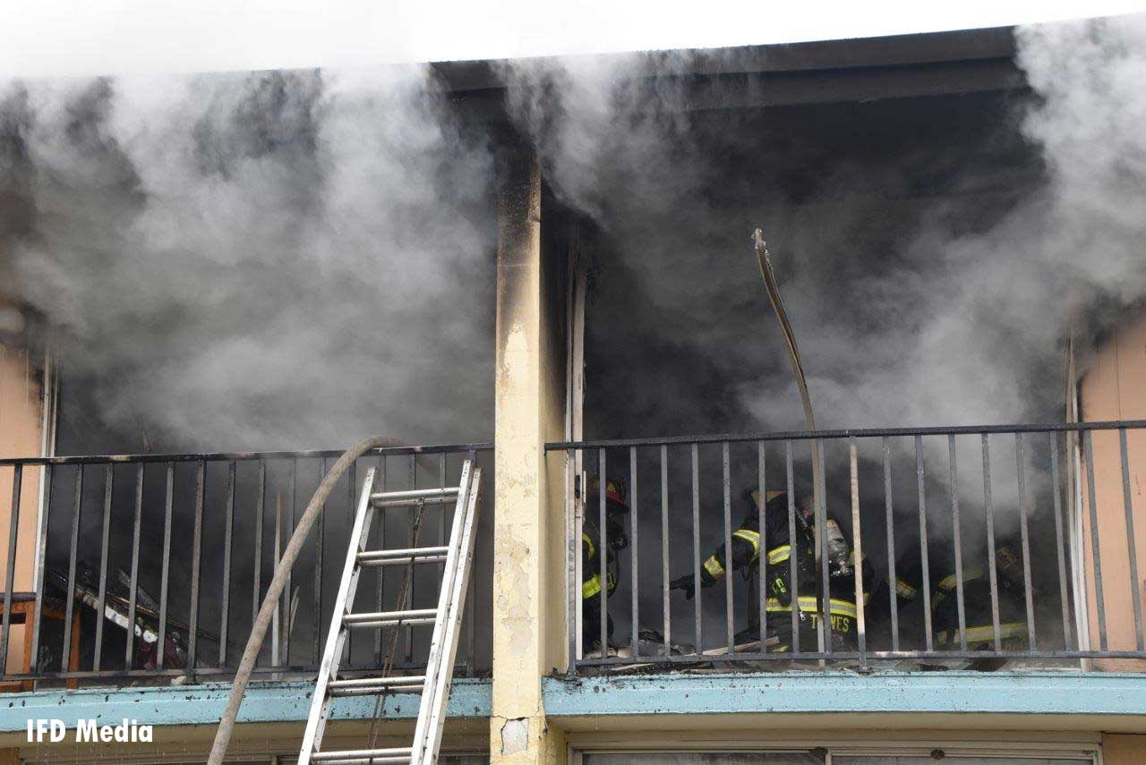 Hose stretched up ground ladder to location in motel