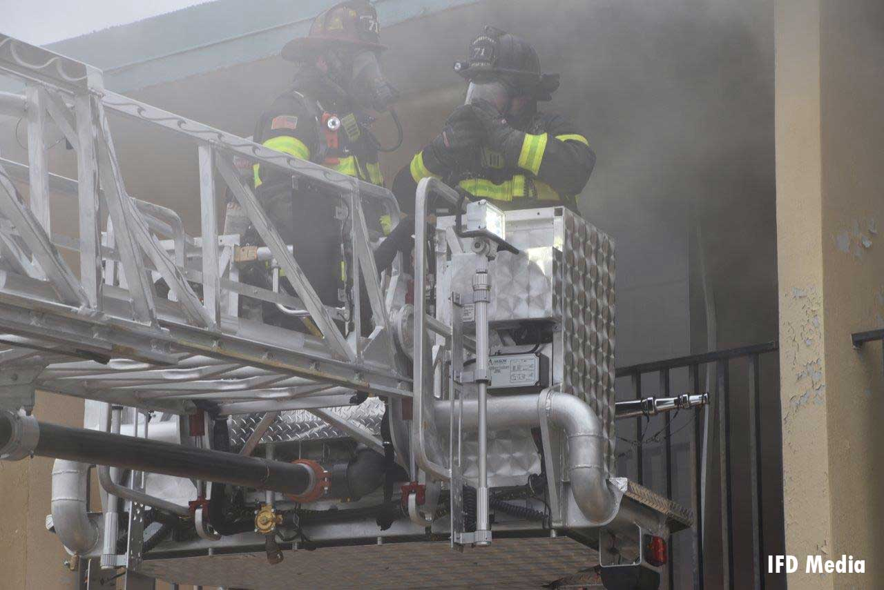 Firefighters in tower ladder bucket at motel fire