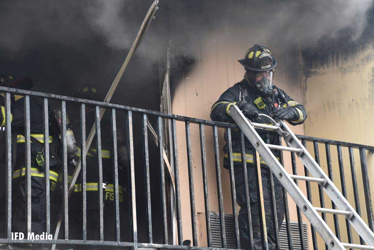 Firefighters on balcony with ladder and smoke