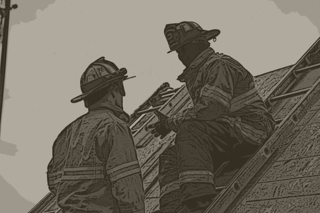Firefighter on a ladder talking to another firefighter