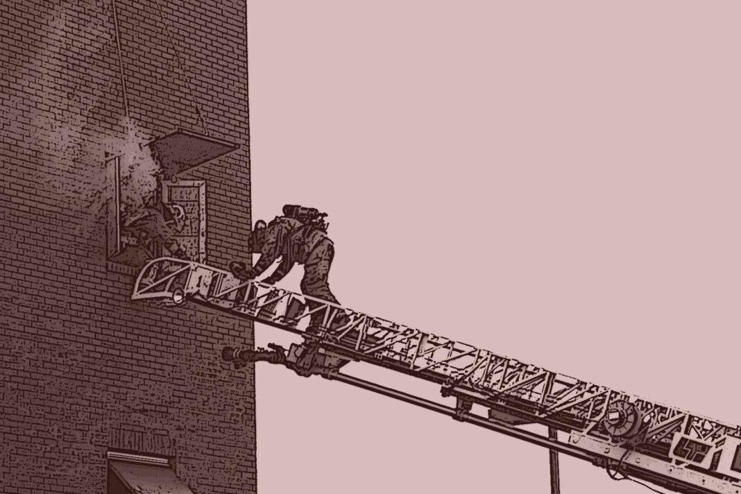 Firefighters climbing an aerial ladder