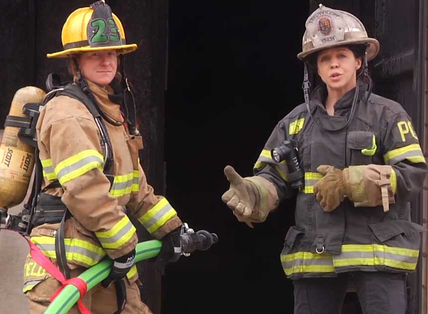 Katie Johnson and another firefighter using webbing for hoseline control