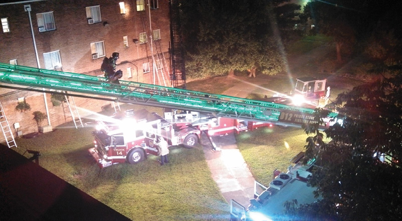 Although the two aerial apparatus are positioned on the grass at side C of this apartment fire, both have spotted the outriggers safely on the concrete sidewalk, saving personnel about 300 yards of travel and giving a well-lit working area for crews. (Photos by author unless otherwise noted.)