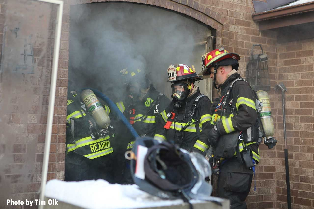 Firefighters advancing a line inside a home.