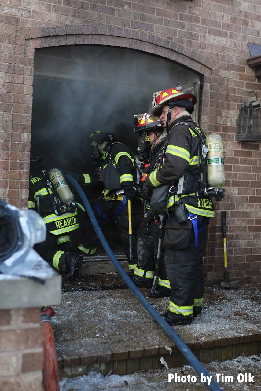 Firefighters with a hoseline advance into a house