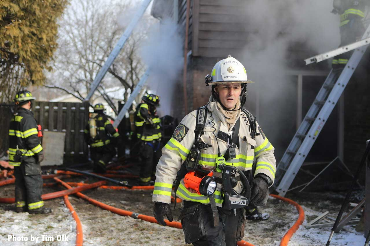 A fire officer with firefighters working behind him