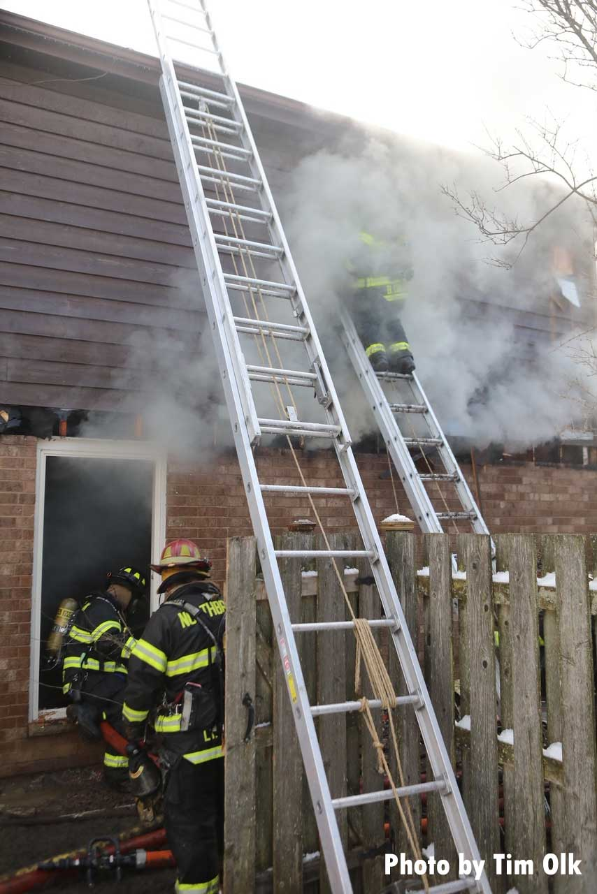 Firefighters on ground ladders at a house fire