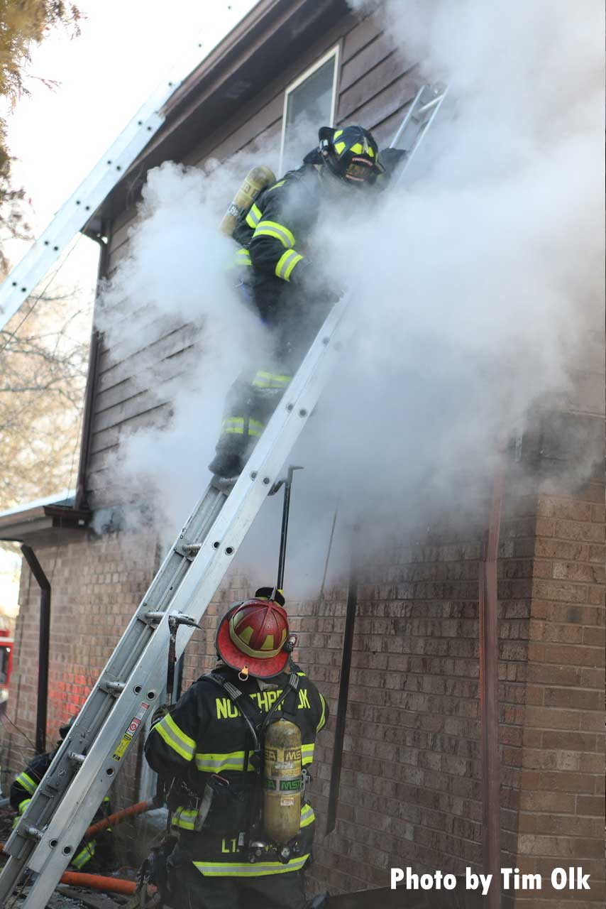 A firefighter on a portable ladder wreathed in smoke