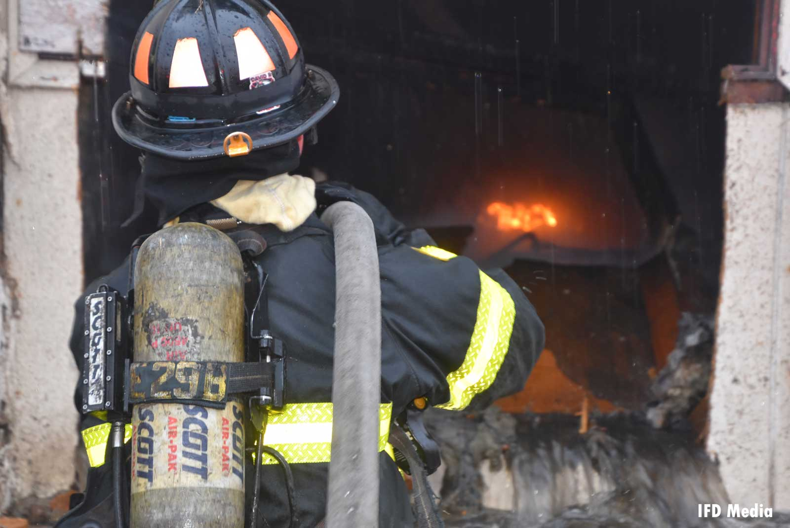 Firefighter with a hoseline over his shoulder confronting the flames
