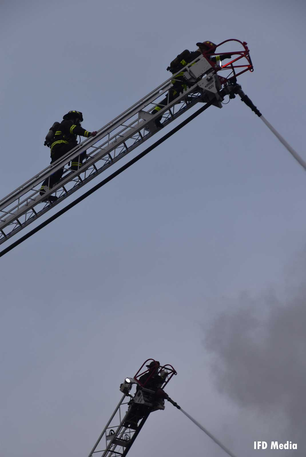 Firefighters on aerial ladders at the fire