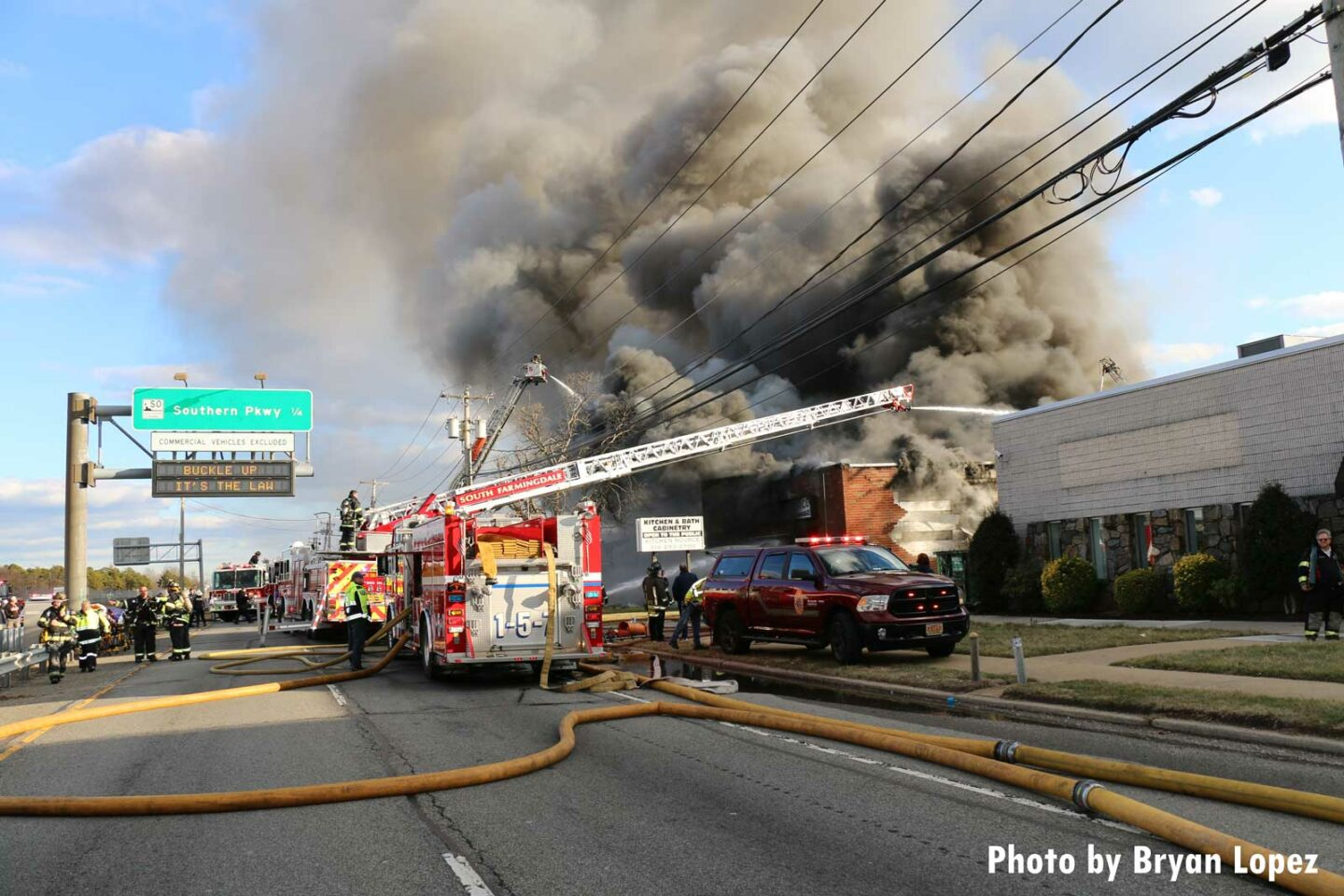 Aerial device in use over large commercial building on Long Island with smoke condition