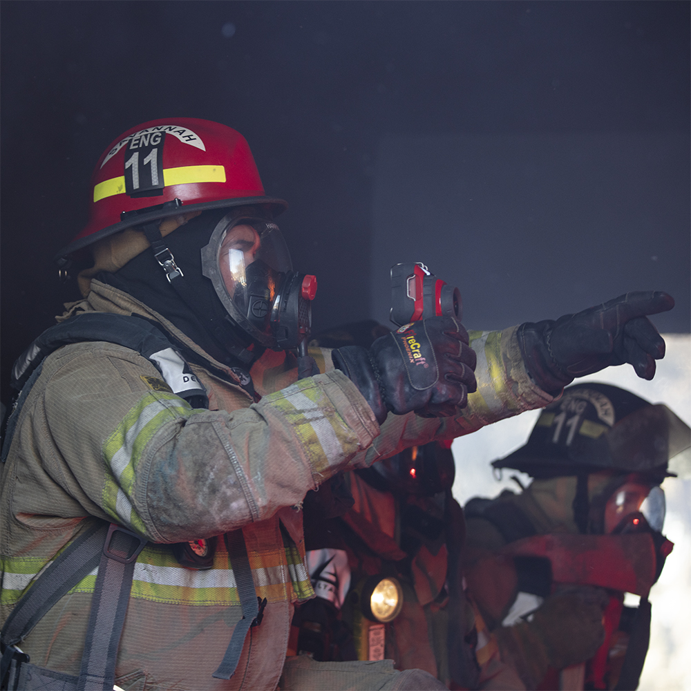 Firefighter using a thermal imaging camera