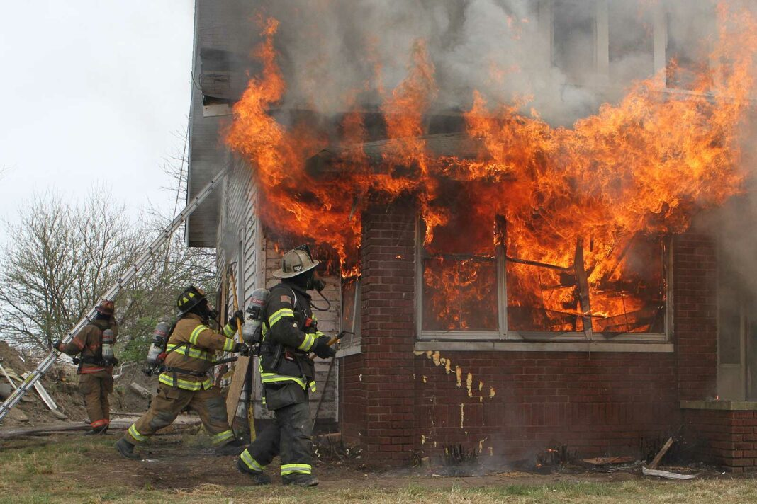 Firefighters confront a large volume of fire in a home