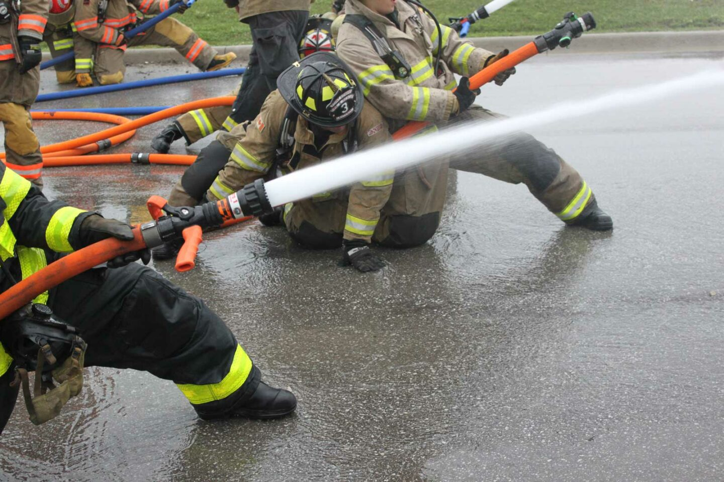 A firefighter on the nozzle extends his leg to check the floor surface in front of him.