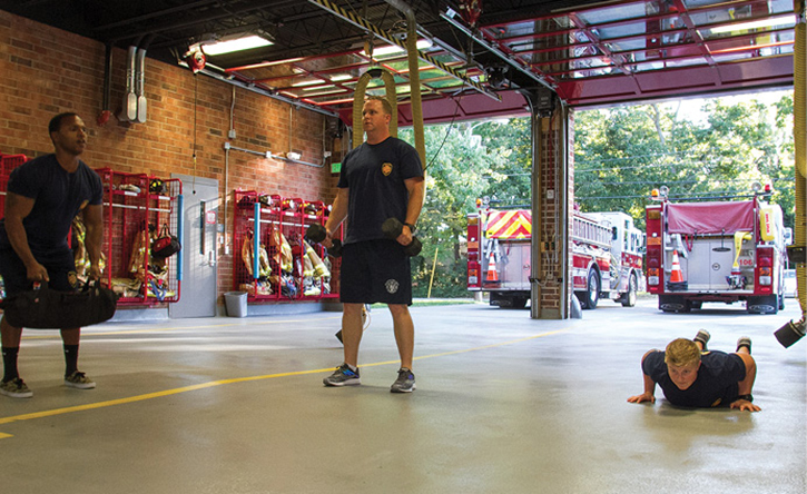 Firefighters work through a five-station circuit (four rounds at 45 seconds per station) to build muscular endurance. The firefighter at left performs sandbag cleans; in the middle, curls; and at right, a hand release pushup.