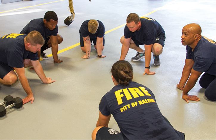 Firefighters work on range of motion and flexibility as a cool-down to an exercise session.