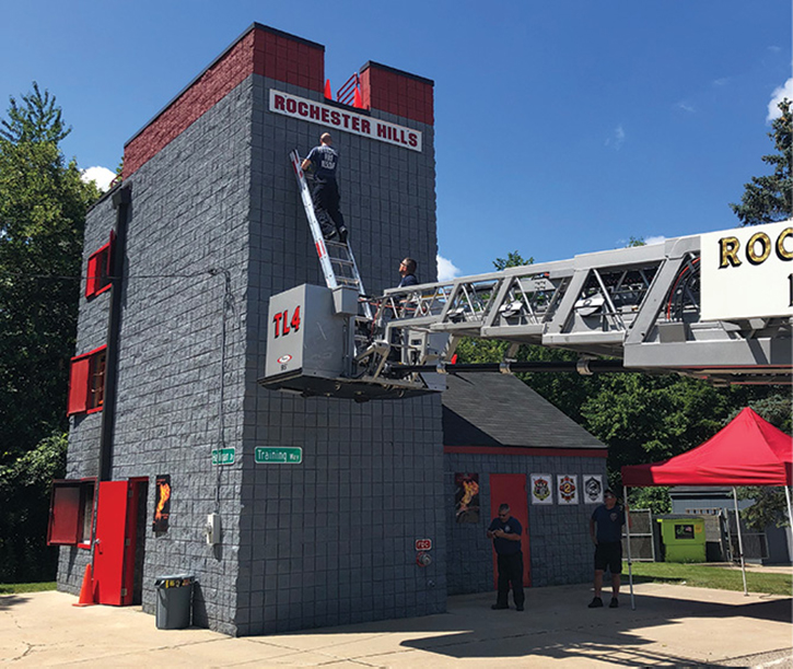 You may have to extend the tower ladder boom under an overhead obstruction and may not be able to increase its elevation, so you may have to use the portable ladder to complete the rescue operation.
