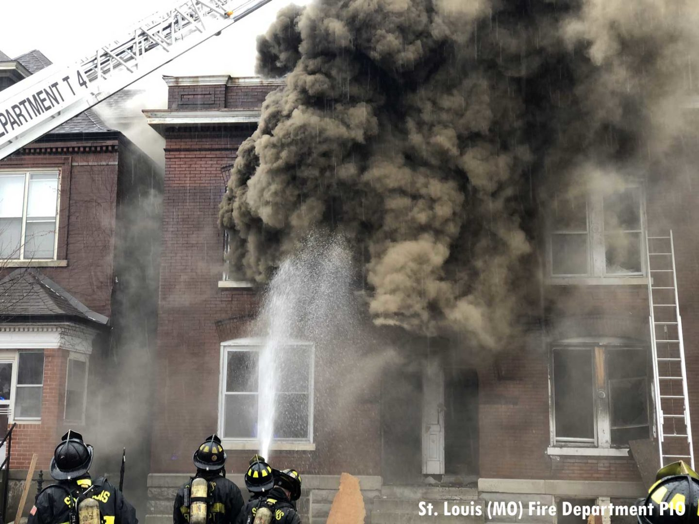 Firefighters observe smoke pouring from vacant building