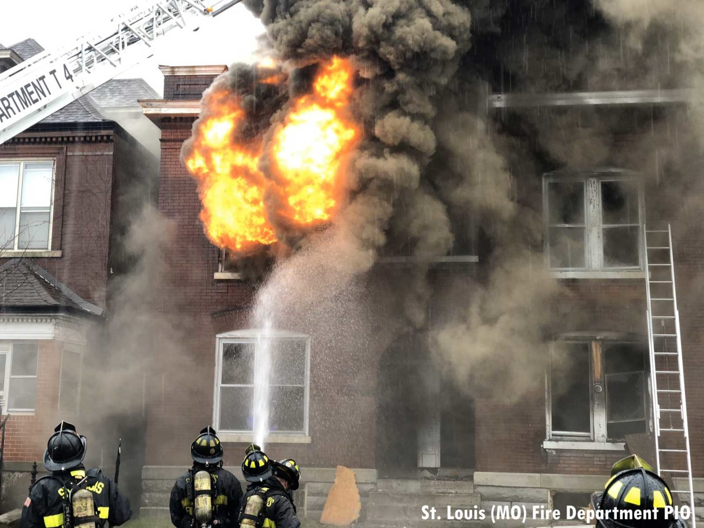 Fire erupts from the building even as firefighters administer water