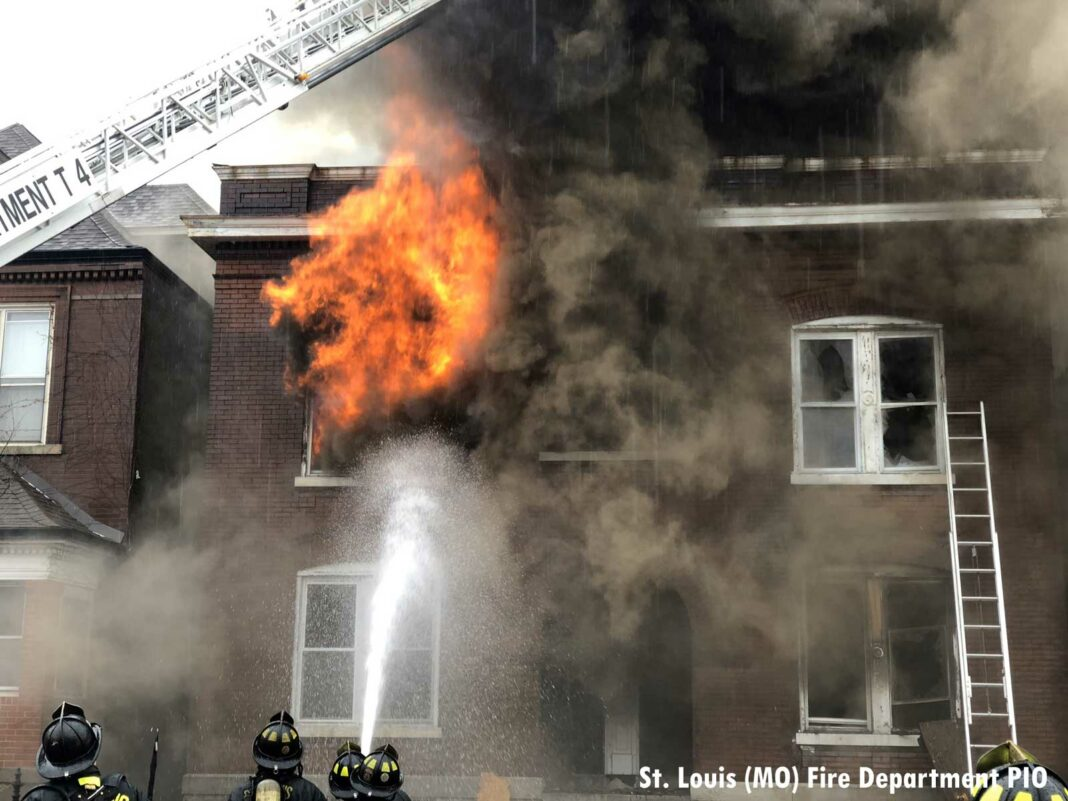 Roaring flames from the building as St. Louis firefighters operate an exterior hose stream