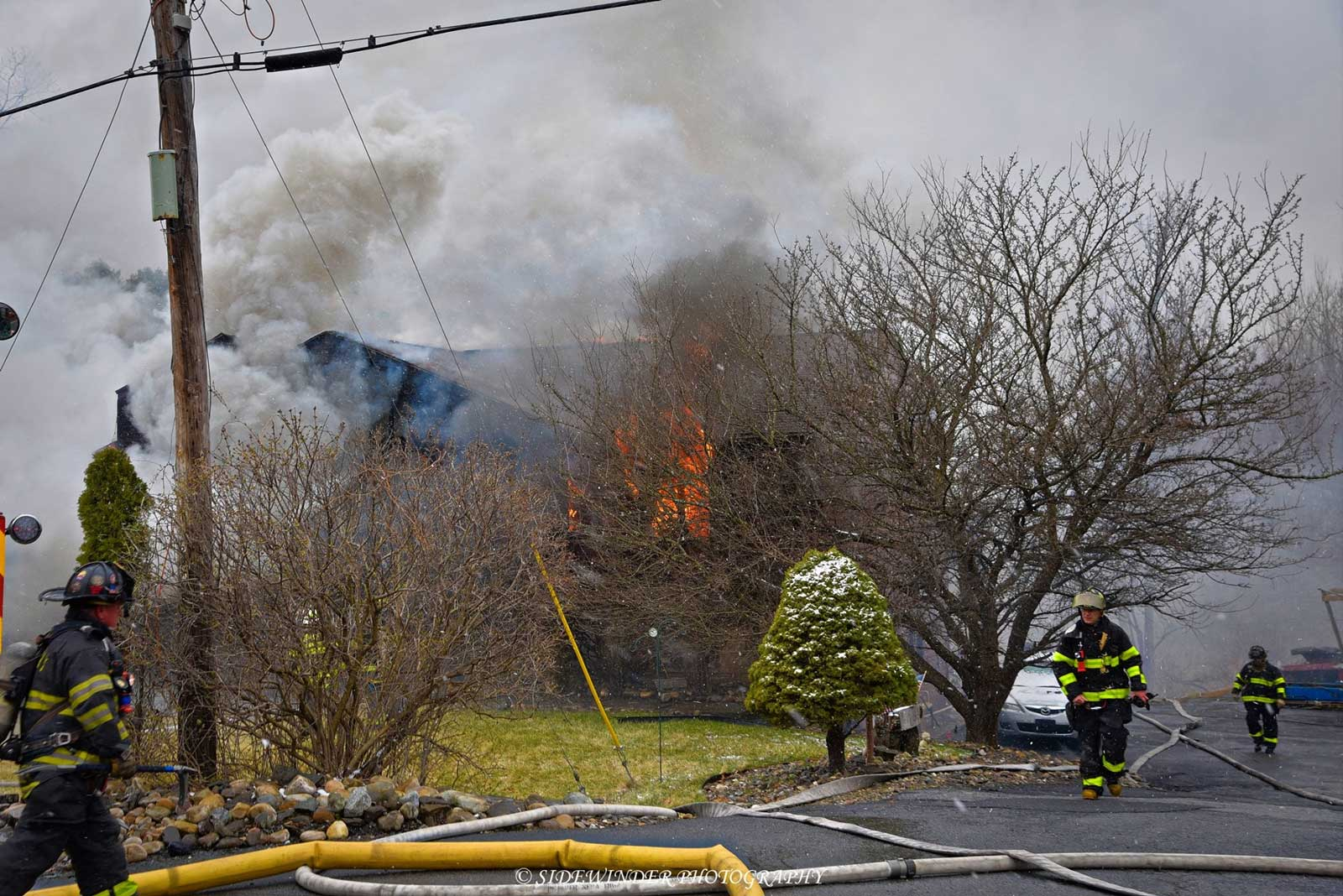 A view of hoselines and fire at the scene
