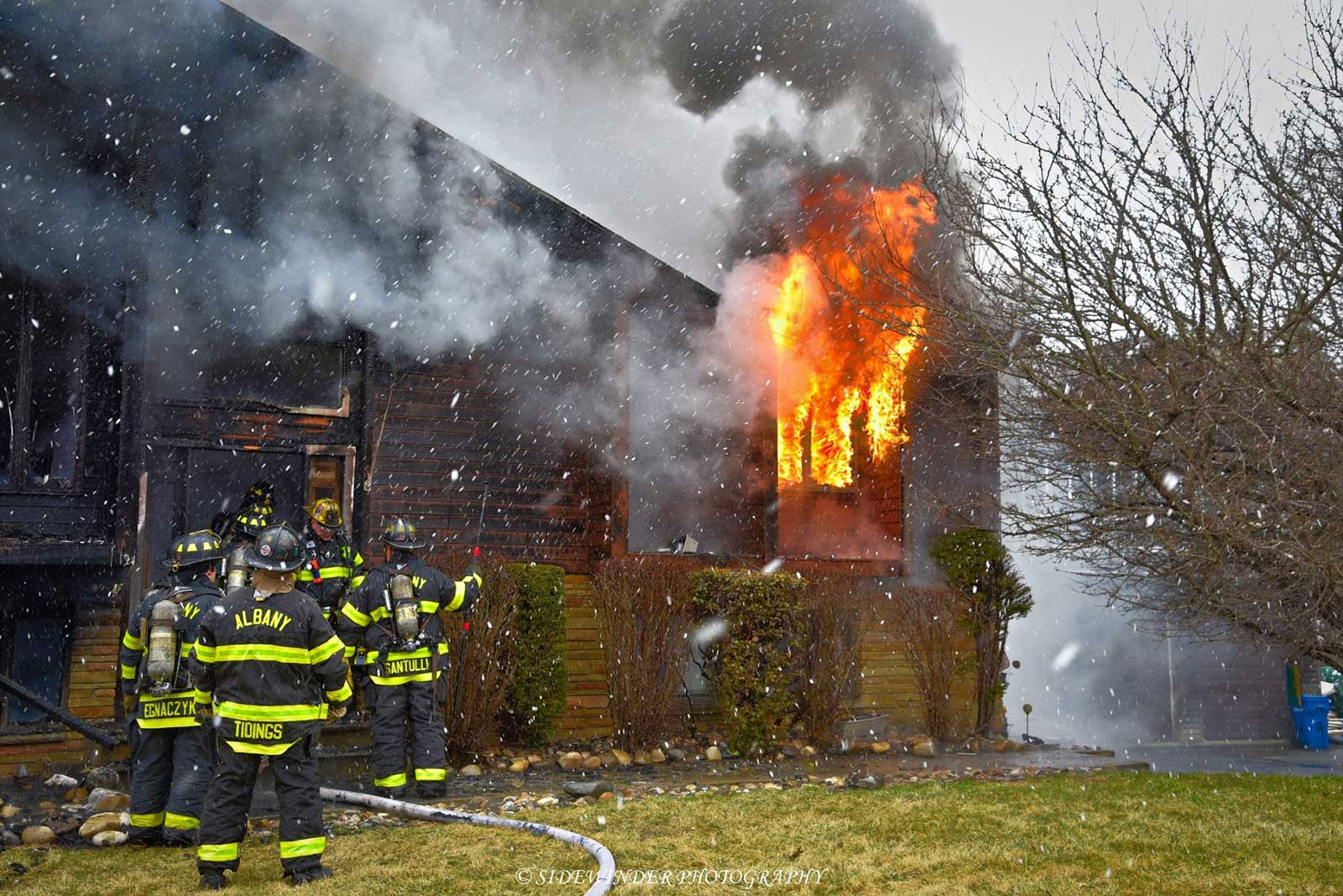 Fire pours from a window as firefighters are poised outside the structure with hoselines